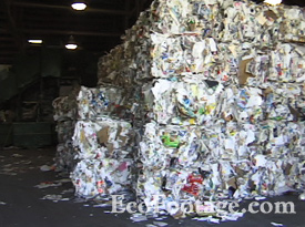 Stacked bales of recycled magazines and mixed paper.