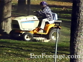 Woman cutting grass with riding lawn mower.